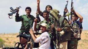 Des combattants anti-Kadhafi brandissent leurs armes.