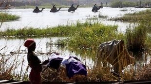 FILE PHOTO: Men on camels cross the water as a woman washes clothes in Lake Chad in Ngouboua, January 19, 2015. REUTERS/Emmanuel Braun/File Photo