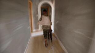 Un combattant libyen des forces gouvernementales soutenues par l'ONU court dans une maison de Syrte, le 19 juillet 2016.