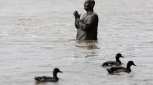 Estátua de Sri Chinmoy está parcialmente submersa em Praga, depois da cheia do rio Vltava.