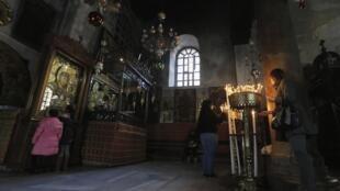 Turistas acendem velas em frente à Igreja da Natividade em Belém, neste 23 de dezembro de 2013.