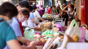 6月8日台北一處購物街,人們佩戴口罩防疫
