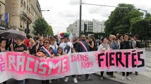 """Manifestantes carregam faixa """"Sem racismo no nosso orgulho""""."""