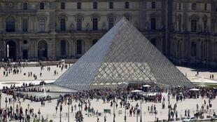 A view shows tourists walking past the Louvre Pyramid designed by Chinese-born U.S. architect Ieoh Ming Pei outside the Louvre Museum in Paris, France, July 4, 2019.