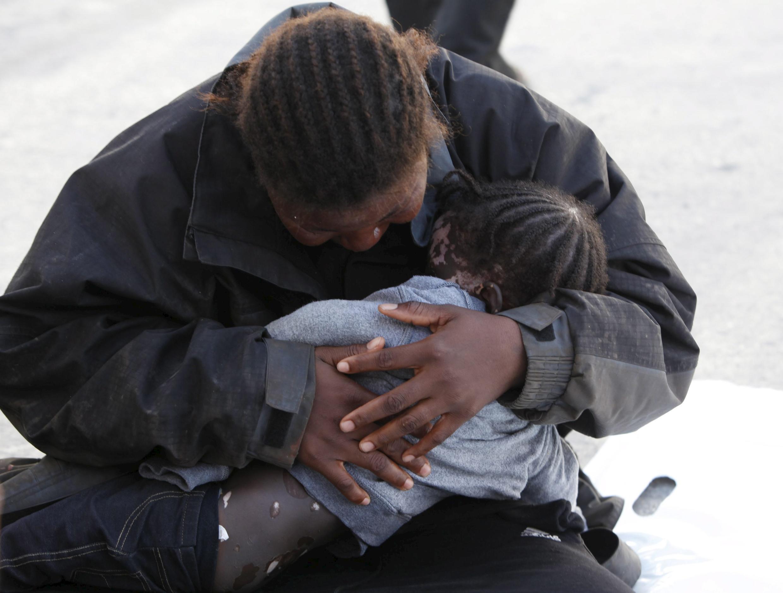 Migrante segura bebê que morreu durante tentativa de travessia do Mediterrâneo, a partir da Líbia.