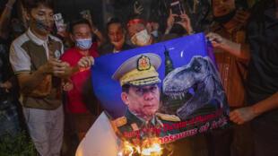 Người Miến Điện sống ở Thái Lan châm lửa đốt bức ảnh tướng Min Aung Hlaing trong cuộc biểu tình trước sứ quán Miến Điện ở Bangkok, ngày 04/02/2021.