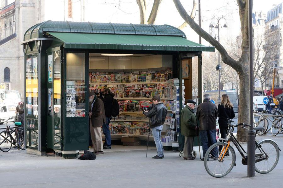 Les gens s'arrêtent dans un kiosque à journaux parisien nouvellement conçu le 14 mars 2017, pour un coût global estimé à 52,4 millions d'euros (56 millions de dollars).