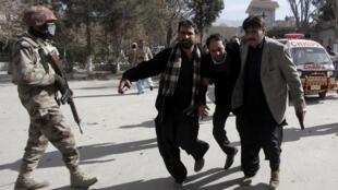 Policiais ajudam fiel a sair da igreja metodista de Quetta, no Paquistão, após o atentado deste domingo 17 de dezembro de 2017.