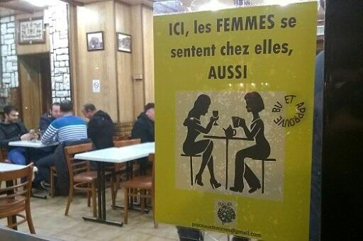"""A poster by a feminist group in a Paris bar reads """"here, women feel at home too"""""""