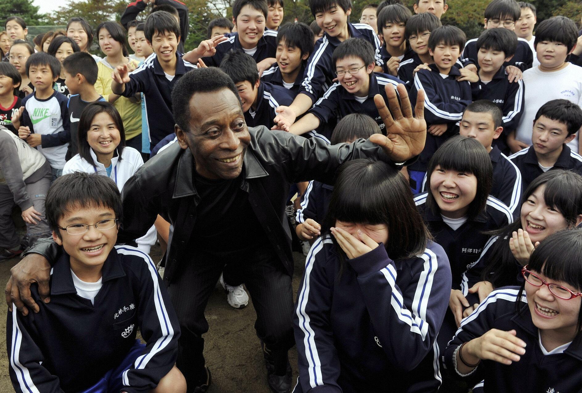 Pelé distribuiu autógrafos durante sua visita a escola em Natori, no Japão.