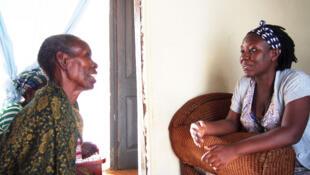 L'infirmière Francesca Nagujja (D) parle avec sa patiente Jennifer (G) qu'elle est venue visiter, le 26 janvier 2018.