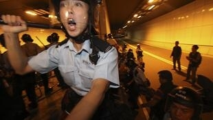 Policías intentan retirar las barricadas erigidas en un túnel de Hong Kong.