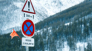Road signs are pictured on a snow-covered road as winter weather bringing snow and freezing temperatures continues in France.
