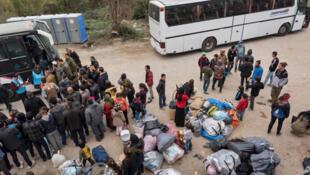 Des familles attendent leur tour pour monter dans un bus qui les transférera depuis des sites de tentes vers des logements en dur.