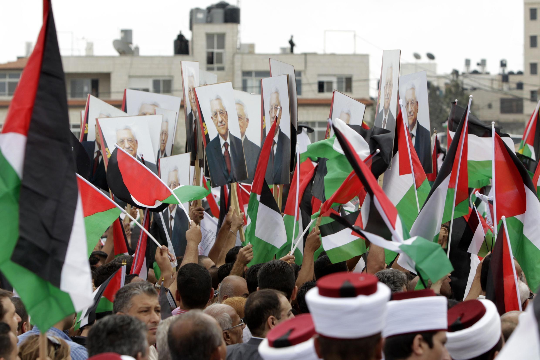 Người Palestine giương cờ và hình ảnh tổng thống Mahmoud Abbas, khi ông Abbas trở về từ Liên Hiệp Quốc, Ramallah, 25/09/2011.