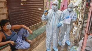 Du personnel médical en combinaison fait du porte-à-porte dans un bidonville de Bombay dans la lutte contre la propagation du coronavirus, début juin 2020.