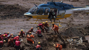 In this file photo taken on January 28, 2019 firefighters receive equipment to open a vehicle found in the mud as they search for victims of a dam collapse at an iron-ore mine belonging to Brazil's giant mining company Vale near Brumadinho in the state of Minas Gerais, southeastern Brazil