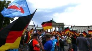 Plus de 5 000 manifestants de l'Alternative pour l'Allemagne, drapeaux à la main, face aux quelque 25 000 personnes réunies pour de bruyantes contre-manifestations (selon les estimations de la police) à Berlin, le 27 mai 2018.