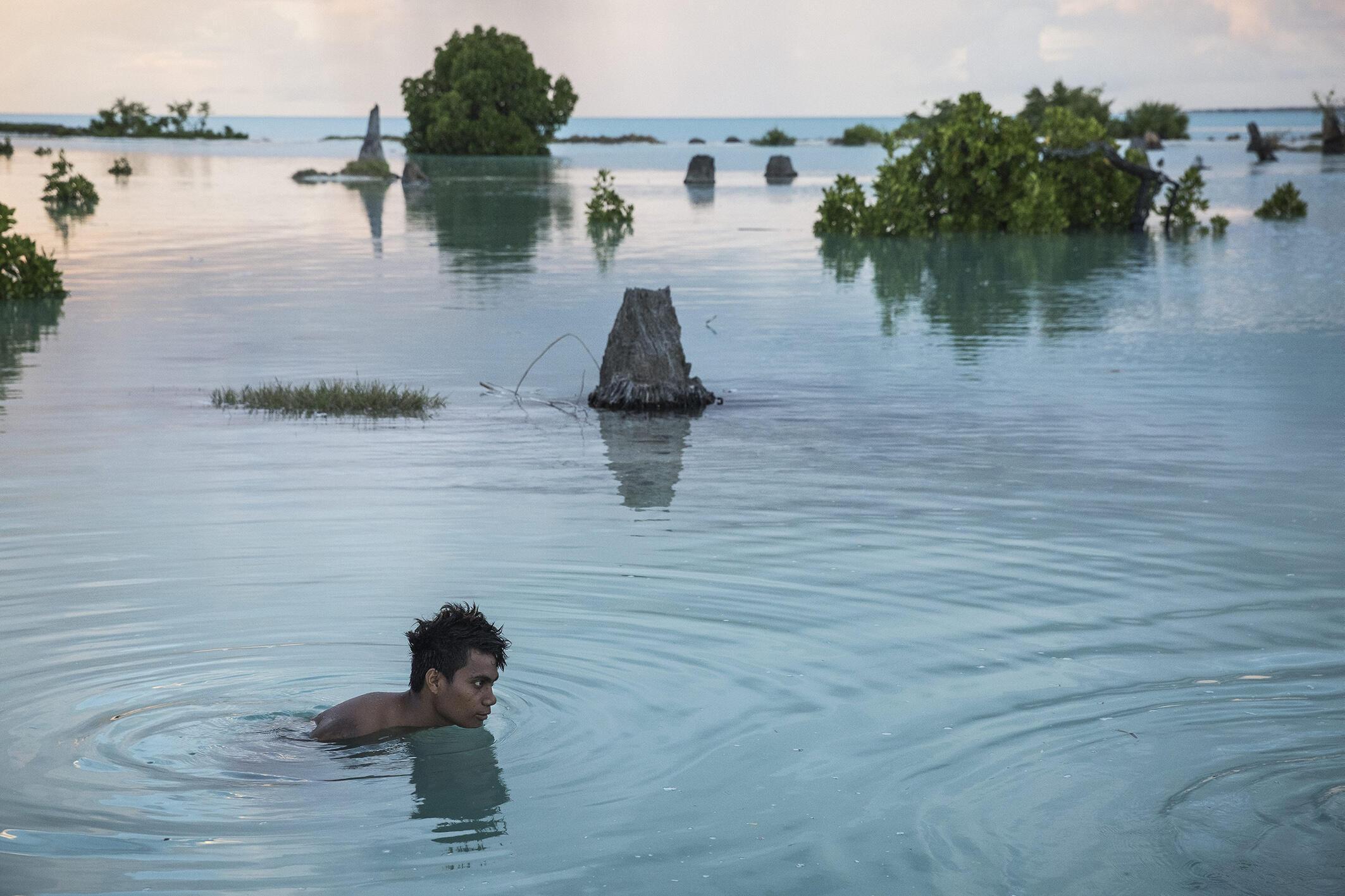 Peia Kararaua (16 ans), dans un quartier inondé du village d'Aberao, îles Kiribati, l'un des pays les plus durement touchés par la montée du niveau des mers.