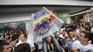 Tel un trophée symbolisant l'autorité, les manifestants brandissent un bouclier anti-émeutes appartenant aux policiers turcs.
