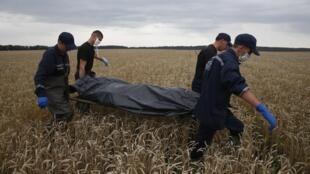 Des membres ukrainiens des services des situations d'urgence évacuent le corps de l'une des 298 victimes du crash du vol MH17, samedi 19 juillet 2014.