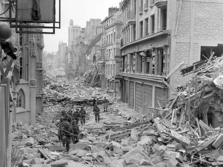 Patrouille de troupes canadiennes dans les rues de Caen, juillet 1944.