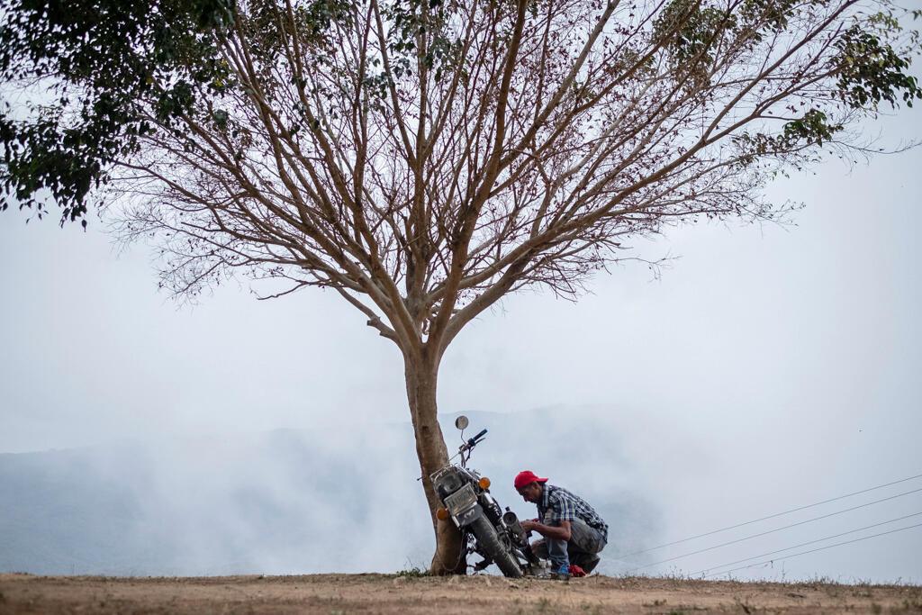 Un homme répare sa moto dans les collines de Ciudad Caribia, entouré de brouillard. Les pièces de rechange coûtent des dizaines de dollars et le salaire minimum est d'à peine 7 dollars.