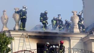A Paris, les pompiers luttent contre l'incendie qui a causé des dégâts irréversibles à l'hôtel Lambert, classé monument historique, le 10 juillet 2013.