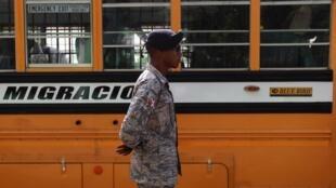 Un soldat dominicain monte la garde face au bus qui doit ramener les migrants vers Haïti, le 24 juin 2015.