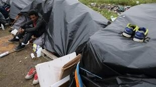 An Erythrean migrant sits outside his makeshift shelter close to a chemical factory in Calais