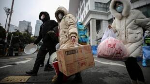 Guéris du coronavirus Covid-19, des patients quittent un des hôpitaux de campagne à Wuhan, le 9 mars 2020.