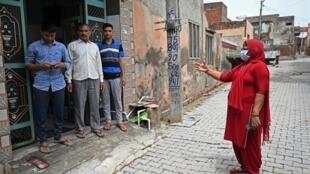 Una trabajadora de la salud (derecha) habla a una familia durante una campaña de concientización sobre la vacunación en el pueblo de Kalwa village, en el estado indio de Haryana