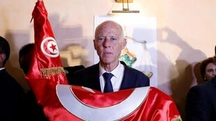 Kais Saied holds Tunisian flag after exit poll results were announced in runoff in Tunis, Tunisia October 13, 2019