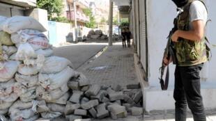 Combatente curdo observa rua de Cizre, na fronteira entre a Síria e a Turquia.