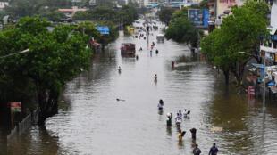 Personas caminan por una calle inundada tras las fuertes lluvias en Bombay, India, el 16 de julio de 2021
