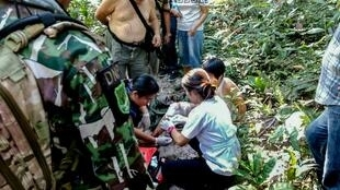 Muriel Benetulier (partially obscured) is tended to by Thai medics and Park Rangers at  Khao Yai National Park
