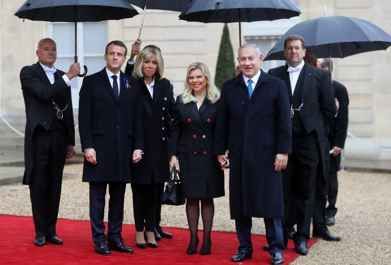 French President Emmanuel Macron (L) and his wife Brigitte Macron welcome Israel's Prime Minister Benjamin Netanyahu and his wife Sara at the Elysee Palace in Paris on November 11, 2018.