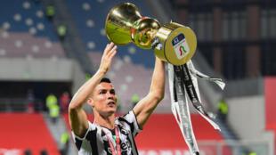 L'attaquant portugais de la Juventus, Cristiano Ronaldo, brandit le trophée de la Coupe d'Italie remportée par son club face à l'Atalanta Bergame, à à Reggio d'Emilie, le 19 mai 2021