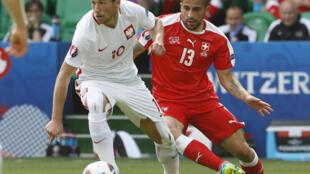 Partido Suiza-Polonia, el polaco Grzegorz Krychowiak en acción seguido del suizo Ricardo Rodriguez este sábado 25 de junio en Saint Etienne, en el primer partido de octavos de final de la Eurocopa 2016.