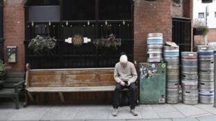 Un homme est assis à l'extérieur d'un bar fermé à Belfast, en Irlande du Nord, le vendredi 16 octobre 2020.
