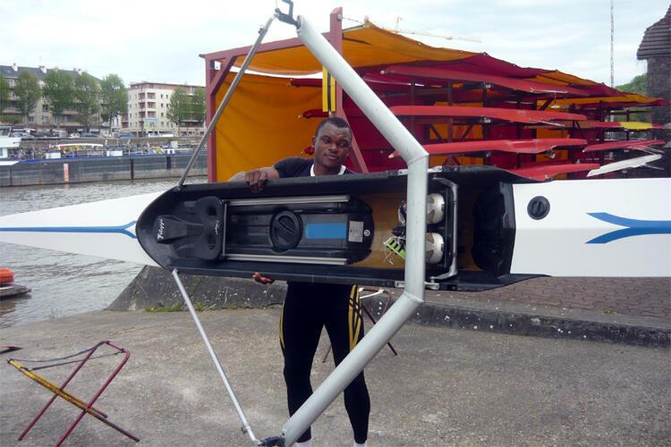 Le Camerounais Paul Etia Ndoumbé range son skiff dans un hangar après l'entraînement.