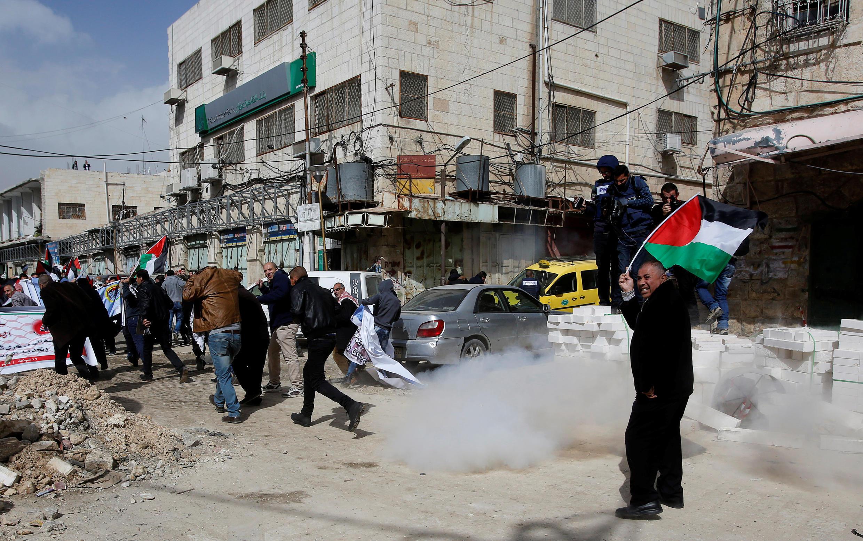 Des manifestants palestiniens chassés par les gaz lacrymogènes des soldats israéliens, à Hébron, le 16 février 2018.