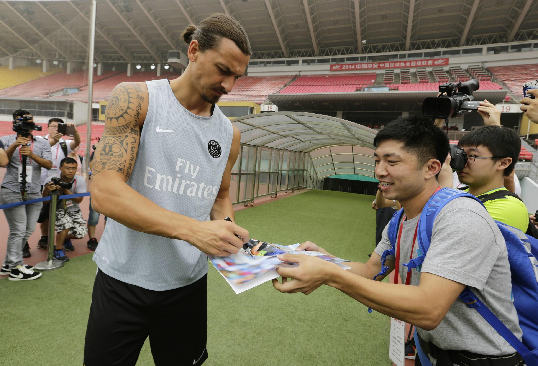 Zlatan Ibrahimović (G) signe un autographe pour un de ses fans à Pékin, le 31 juillet 2014.