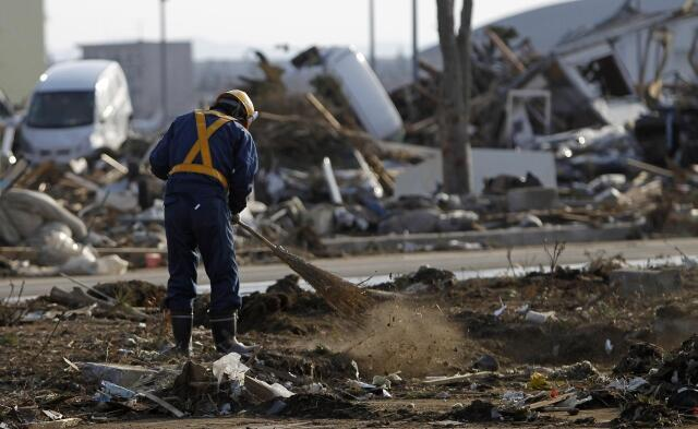 Funcionarios japoneses limpam a região de Sendai, atingida pelo terremoto e tsunami.
