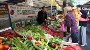 Un stand de vente de fruits et légumes bio, dans un marché à Paris.