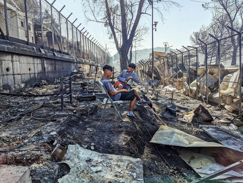 Dos inmigrantes sentados sobre restos en el quemado campo de refugiados de Moria, en la isla griega de Lesbos, el 9 de septiembre de 2020
