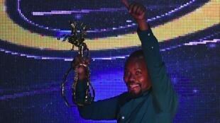 Rwandan film director Joel Karekezi holds up the Yennega Stallion trophy after winning best film at FESPACO, Ouagadougou, Burkina Faso, 2 March, 2019