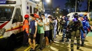 Manifestantes são escoltados pela polícia fora do campus da Universidade Politécnica de Hong Kong (PolyU) durante confrontos com a polícia em Hong Kong, China 18 de novembro de 2019.