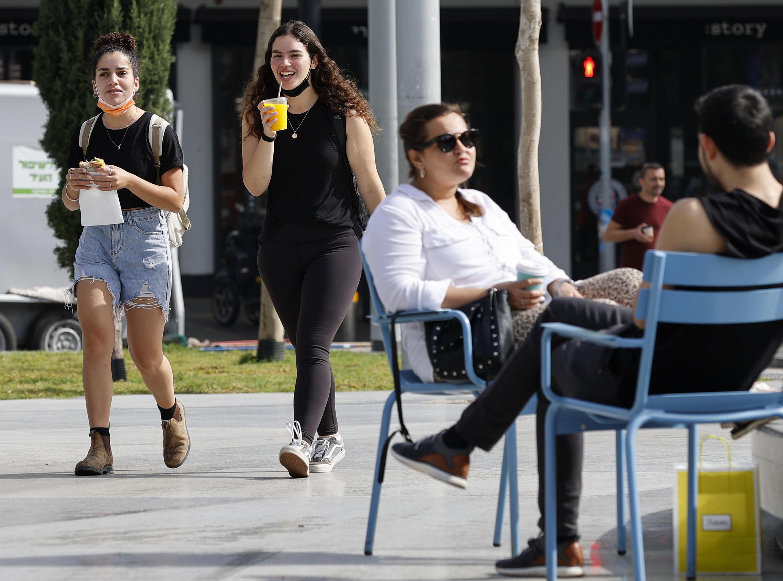 Personas caminan por una calle de la ciudad costera israelí de Tel Aviv después de que las autoridades anunciaran que las mascarillas para la prevención del Covid-19 ya no eran necesarias en el exterior