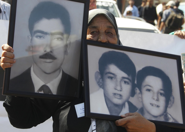 Una mujer palestina muestra fotos de sus familiares matados durante la masacre, este 18 de septiembre en Beirut.